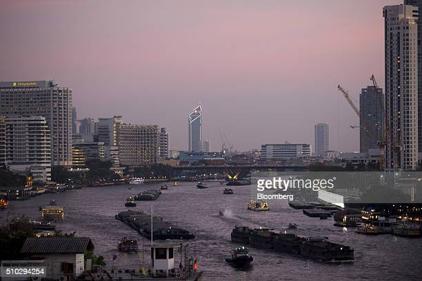 Boats travel past commercial and residential buildings on the Chao Phraya river in Bangkok Thailand on Saturday Feb 13 2016 Thailand's gross domestic...
