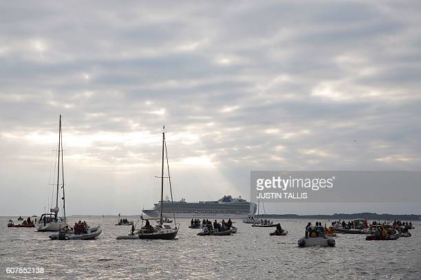 Boats wait for the tide to go out as teams get ready to play a cricket match in the middle of The Solent on the Brambles sandbank which appears for a...