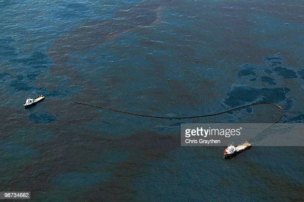 Boats work in tandem to collect oil that has leaked from the Deepwater Horizon wellhead in the Gulf of Mexico on April 28 2010 near New Orleans...