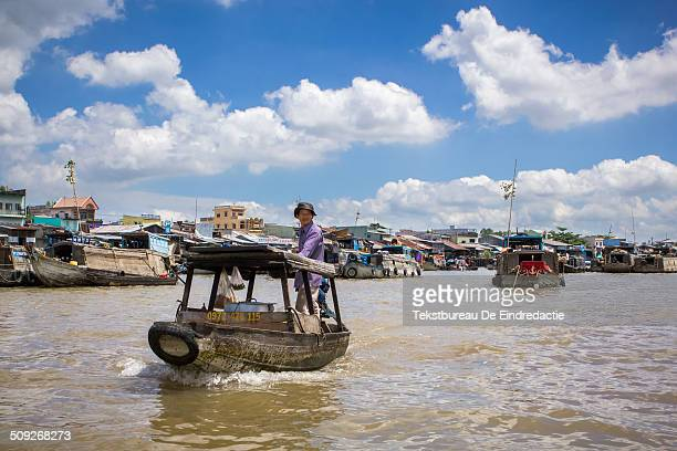 A boatsman steering his small boat across the river early in the morning under a blue sky with clouds at Cai Rang Floating Market near Can Tho Mekong...