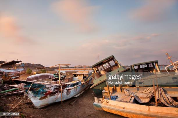 boatyard full of derelict boats in bali - waimea bay stock photos and pictures