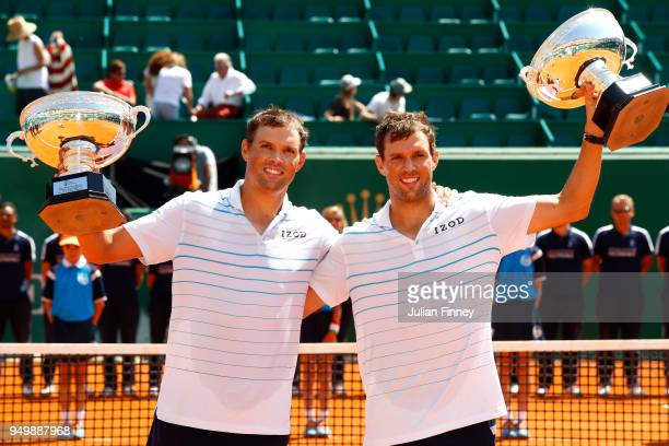 Bob and Mike Bryan of USA celebrate their victory over Oliver Marach of Austria and Mate Pavic of Croatia with the trophy in the doubles final during...