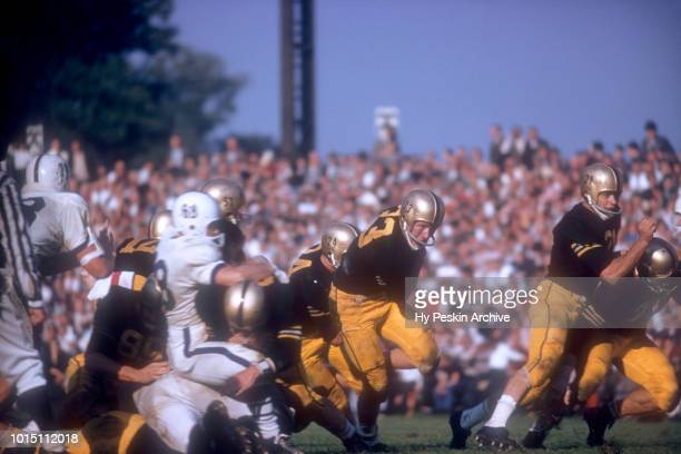 Bob Anderson and Harry Walters of the Army Cadets block as Pete Dawkins runs with the ball during an NCAA game against the Penn State Nittany Lions...