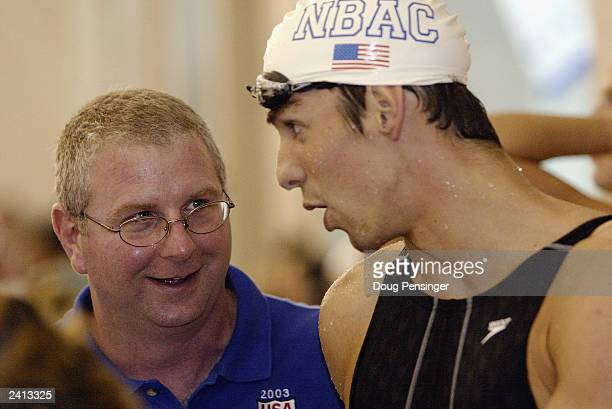 Bob Bowman, coach, checks in with Michael Phelps of the North Baltimore Aquatics Club from Maryland after he took the gold and set an american record...