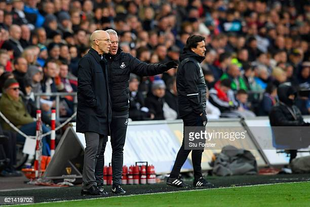 Bob Bradley, Manager of Swansea City in conversation with Alan Curtis during the Premier League match between Swansea City and Manchester United at...