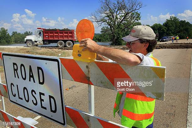 Bob Broadwater of the Mississippi Department of Transportation constructs a barricade across Highway 61 as workers build a levee on the roadway May...