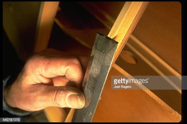 Bob Brunswick uses a chisel to shape cedar on a Pocock racing shell Seattle Washington