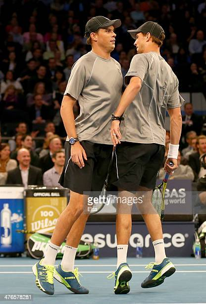 Bob Bryan and Mike Bryan chest bump after winning the first point over John McEnroe and Patrick McEnroe during their doubles match in the BNP Paribas...