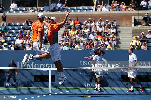 Bob Bryan and Mike Bryan of the United States celebrate match point with a chest bump as Leander Paes of India and Radek Stepanek of the Czech...