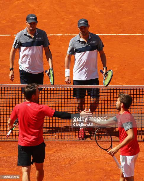 Bob Bryan and Mike Bryan of the United States shake hands at the net after retiring in the first set due to Bob Bryan receiving an injury playing...
