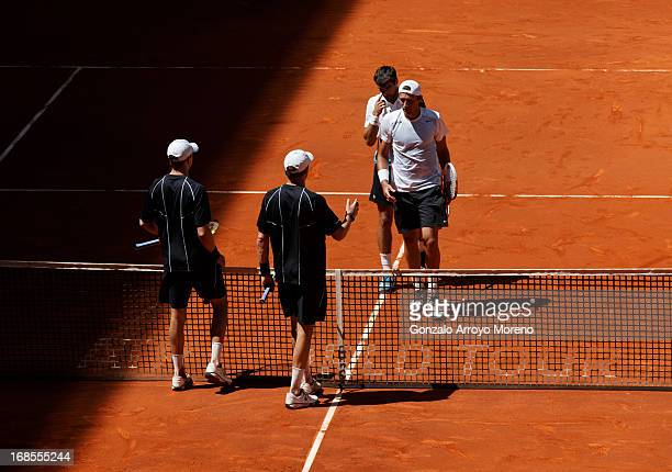 Bob Bryan and Mike Bryan of the US greet Jeremy Chardy of France and Lukasz Kubot of Poland after winning their semi-final doubles match on day eight...