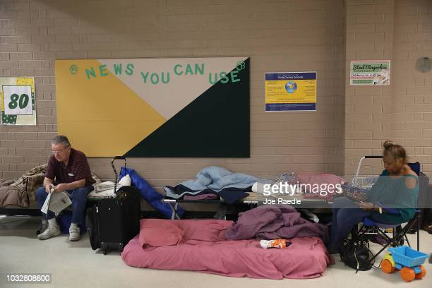 Bob Cavanagh and Linda Moore wait in an evacuation shelter setup at the Conway High School for the arrival of Hurricane Florence on September 13,...