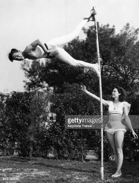 Bob Colpitts un ancien jockey reconverti en acrobate s'entraîne à la perche en compagnie de Mary Nickorson une acrobate aérienne le 14 janvier 1936 à...
