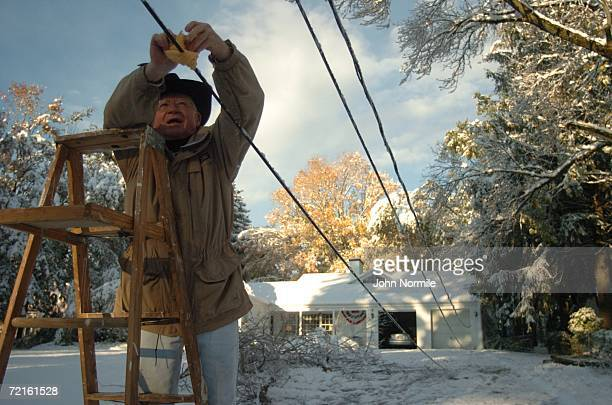 Bob Cornelius hangs a warning flag on a downed powerline October 13, 2006 outside of Buffalo in Orchard Park, New York. A rare and record breaking...