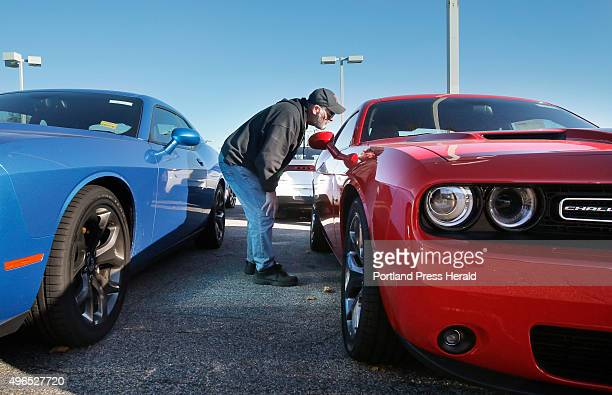 Bob Cournoyer of Lewiston looks inside a Dodge Challenger at Lee Auto Mall in Westbrook on Monday November 9 2015 The Challengers range in price...