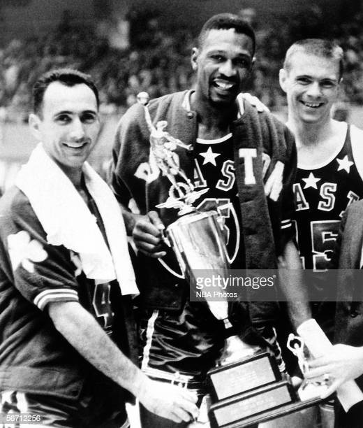 Bob Cousy, Bill Russell and Tom Heinson of the Boston Celtics pose with Bill Russell's NBA All-Star MVP Trophy after the 1963 NBA All Star Game circa...