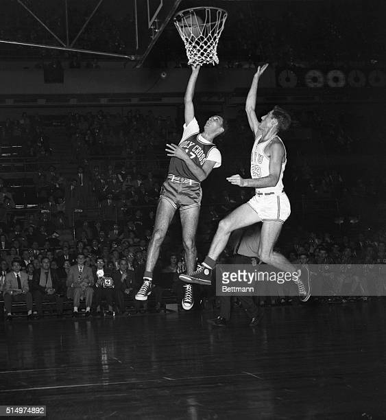 Bob Cousy of Holy Cross is shown sinking a basket as NYU's Jerry Remer 923 rushes to the defense too late during tonight's game at Madison Square...