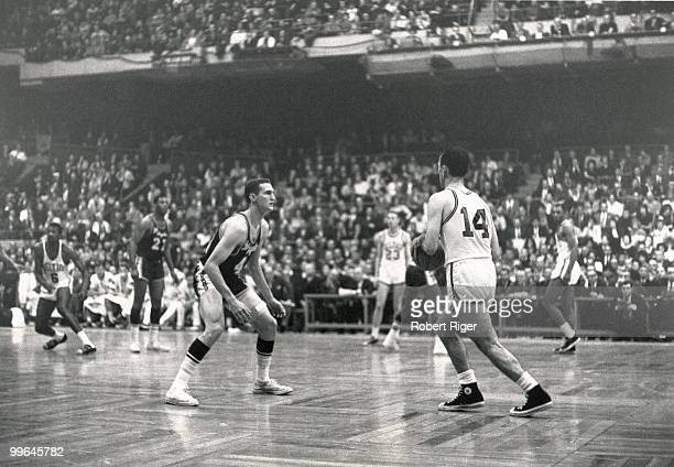 Bob Cousy of the Boston Celtics dribbles against Jerry West of the Los Angeles Lakers during a game in the 196263 season at the Boston Garden in...