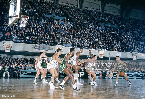 Bob Cousy of the Boston Celtics dribbles the ball as he is defended by Paul Arizin and Wilt Chamberlain of the Philadelphia Warriors during an NBA...
