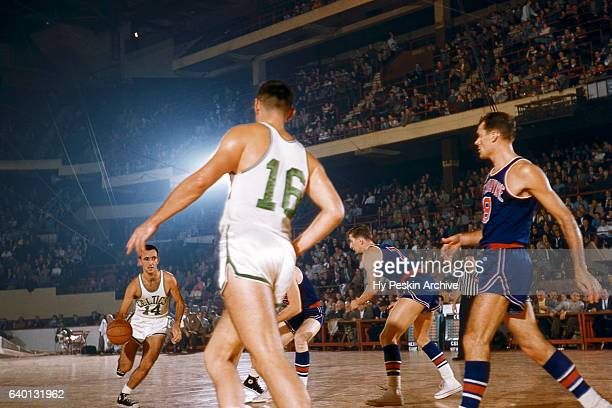 Bob Cousy of the Boston Celtics dribbles the ball as his teammate Jack Nichols looks for a pass during an NBA game against the Ft Wayne Pistons circa...