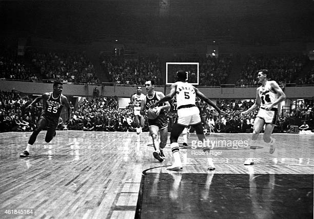 Bob Cousy of the Boston Celtics holds the ball as his teammate KC Jones waits for a pass as Dick Barnett and Jerry West of the Los Angeles Lakers...