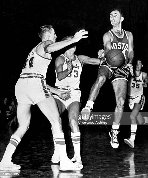 Bob Cousy of the Boston Celtics in midair about to pass to a teammate as Los Angeles Laker players Jerry West and Rod Hundley closed in on him St...