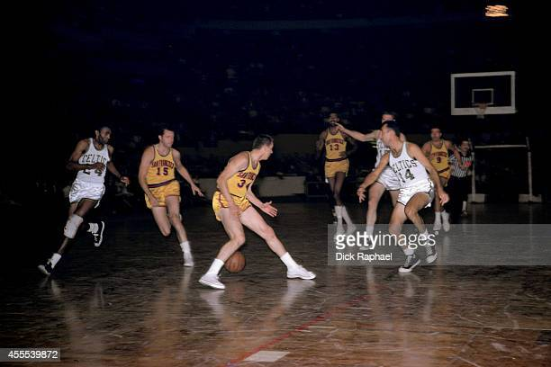 Bob Cousy of the Boston Celtics passes the ball to Sam Jones during a game against the San Francisco Warriors circa 1962 at the Boston Garden in...