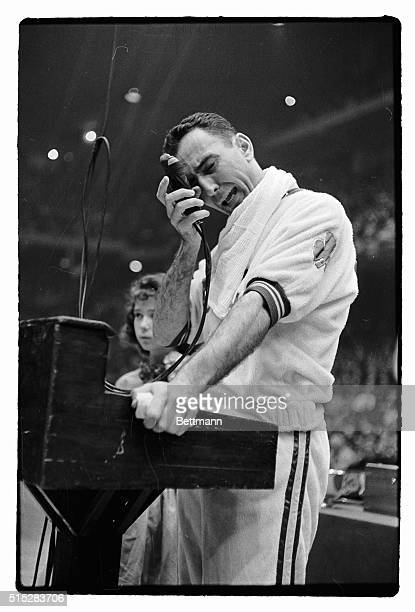 Bob Cousy of the Boston Celtics presses the microphone to his face as he bursts into tears while making a speech to some 15000 fans prior to his last...
