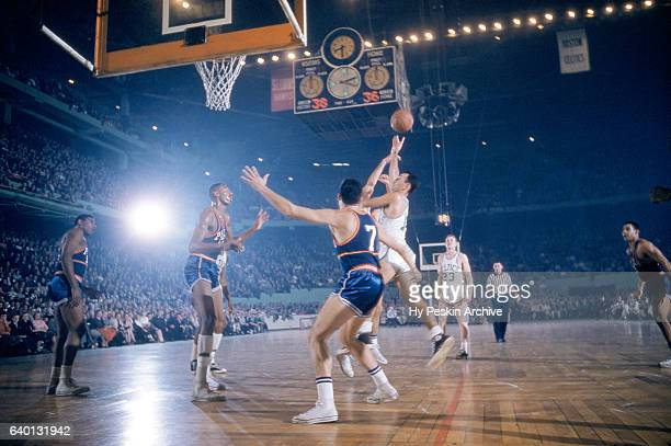 Bob Cousy of the Boston Celtics shoots over Ernie Beck and Wilt Chamberlain of the Philadelphia Warriors during an NBA game circa 1959 at the Boston...