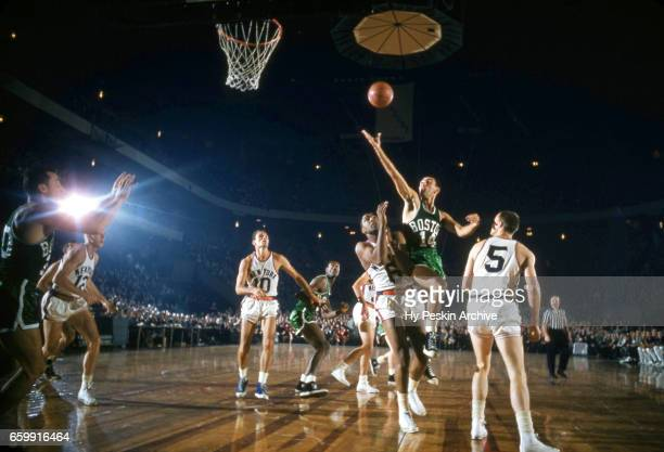 Bob Cousy of the Boston Celtics shoots the layup as Willie Naulls and Guy Sparrow of the New York Knicks defend during an NBA game on October 26 1957...