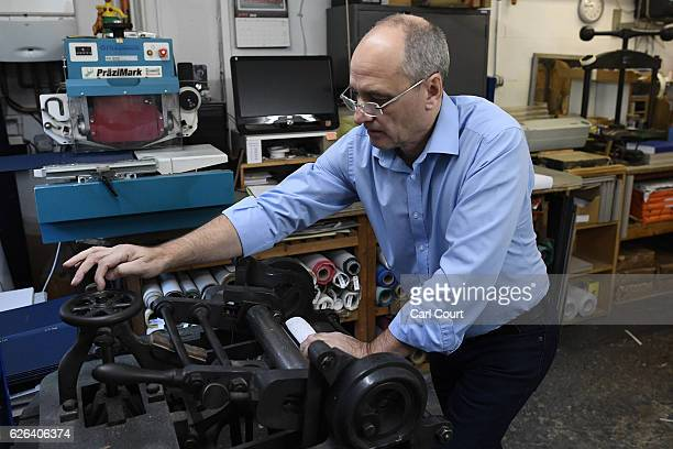 Bob Covington the Head of the Bindery operates a manual machine to round the spine of a book that's being prepared at Collis Bird and Withey...