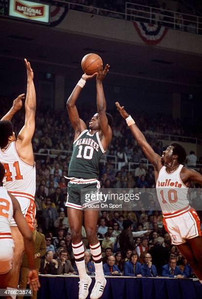 Bob Dandridge of Milwaukee Bucks goes up to shoot over Wes Unseld Earl Monroe of the Baltimore Bullets during an NBA basketball game circa 1972 at...