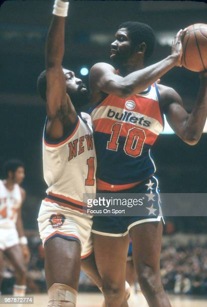 Bob Dandridge of the Washington Bullets looks to pass the ball over the top of Earl Monroe of the New York Knicks during an NBA basketball game circa...