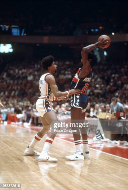 Bob Dandridge of the Washington Bullets looks to pass the ball over the top of Julius Erving of the Philadelphia 76ers during an NBA basketball game...
