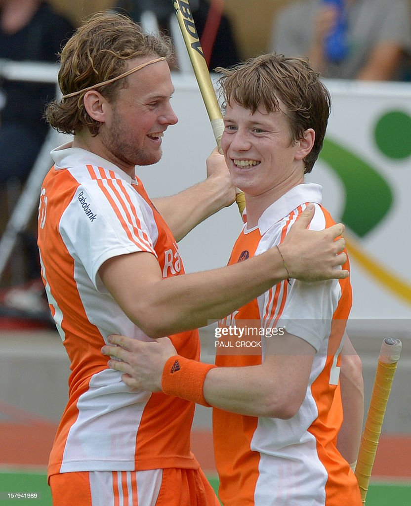 Bob de Voogd of The Netherlands (L) congratulates a smiling Seve van Ass after he scored against Pakistan during their semi final match at the men's Hockey Champions Trophy in Melbourne on December 8, 2012. IMAGE STRICTLY RESTRICTED TO EDITORIAL USE - STRICTLY NO COMMERCIAL USE AFP PHOTO / Paul CROCK