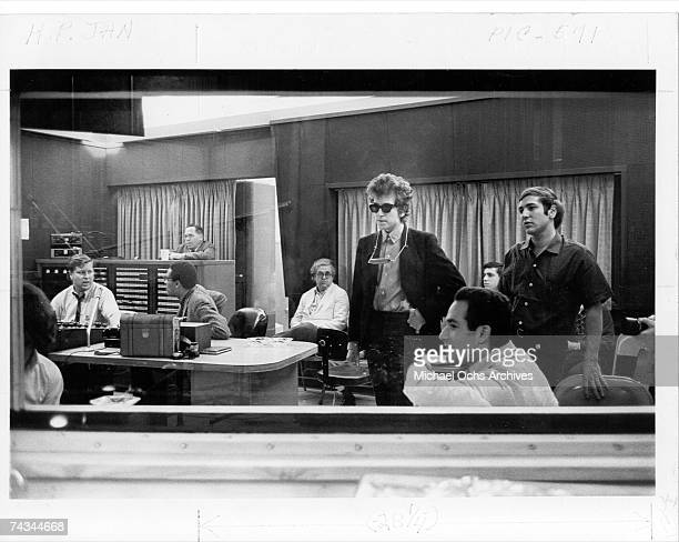 Bob Dylan and his manager Albert Grossman listen back to the recordings of the album 'Highway 61 Revisited' surrounded by engineers and other...