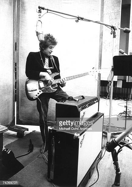 Bob Dylan plays a Fender Jazz bass through a Fender Bassman amplifier with a harmonica around his neck and Ray-Ban sunglasses sitting on the amp...