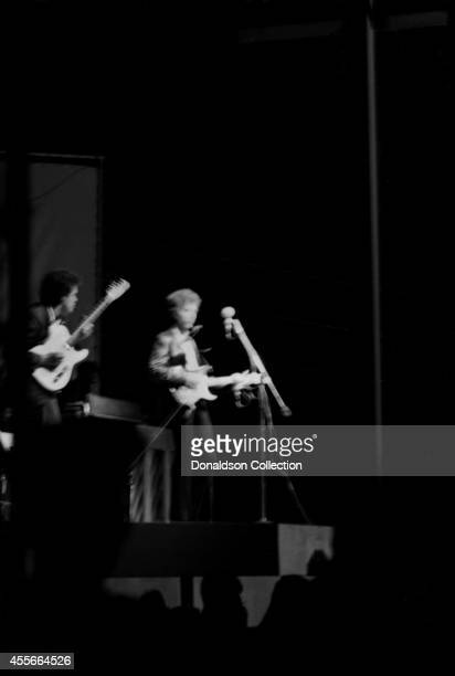 Bob Dylan plays a Fender Stratocaster electric guitar for the first time on stage as he performs at the Newport Folk Festival with guitarist Mike...