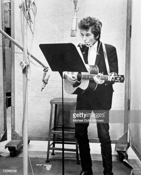 Bob Dylan plays harmonica and acoustic guitar while singing in to a microphone to record his album 'Bringing It All Back Home' on January 13th 1965...