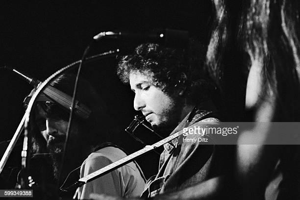Bob Dylan plays his guitar on stage during the 1971 Concert for Bangladesh George Harrison is in the background
