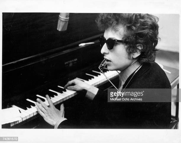 Bob Dylan plays piano with a harmonica around his neck during the recording of the album 'Highway 61 Revisited' in Columbia's Studio A in the summer...