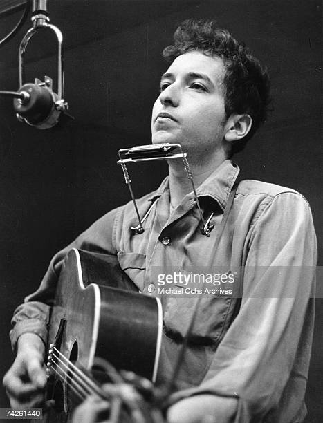 Bob Dylan recording his first album 'Bob Dylan' in front of a microphone with an acoustic Gibson guitar and a harmonica during one of the John...