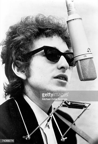 Bob Dylan sing in to a microphone with a harmonica around his neck to record his album 'Bringing It All Back Home' on January 1315 1965 in Columbia's...