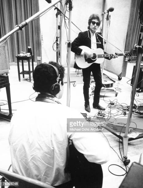 Bob Dylan strums a Gibson acoustic guitar with a harmonica around his neck and wearing RayBan sunglasses while recording his album ´Bringing It All...