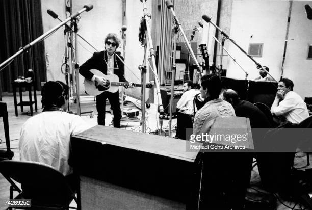 Bob Dylan strums a Gibson acoustic guitar with a harmonica around his neck and wearing RayBan sunglasses with session guitar player Kenny Rankin in...
