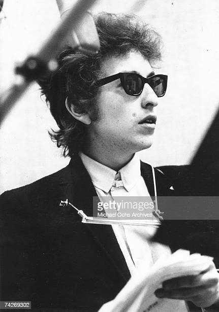 Bob Dylan takes a break with the harmonica around his neck and wearing RayBan sunglasses while recording his album 'Bringing It All Back Home' on...