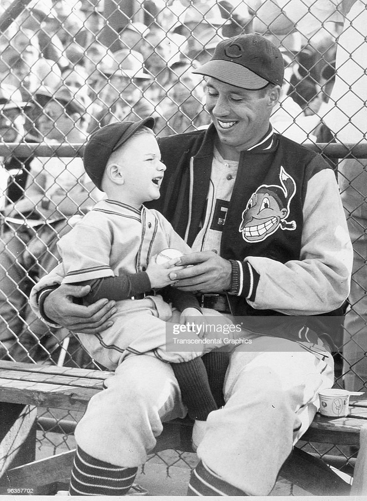 Bob Feller and a young Indians fan share a laugh before a game at Municipal Stadium in Cleveland in 1948.