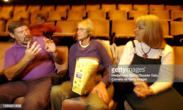 Bob Furman talks using sign language with his wife Ginny Furman and Marie Cacciator before the start of Pirates of the Caribbean at the Colony Square...