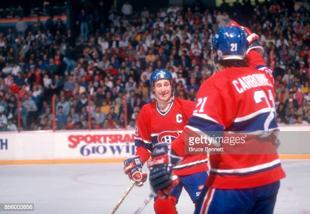 Bob Gainey of the Montreal Canadiens celebrates with teammate Guy Carbonneau after scoring a goal during the 1989 Conference Finals against the...
