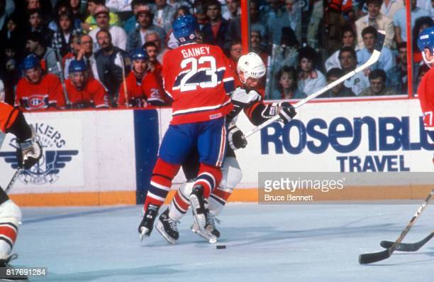 Bob Gainey of the Montreal Canadiens checks Mark Howe of the Philadelphia Flyers during an 1985 Conference Finals game circa May 1989 at the Spectrum...